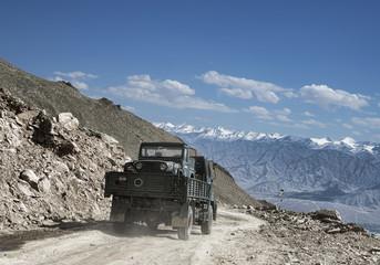 Transportation of army car on truk among mountain landscape