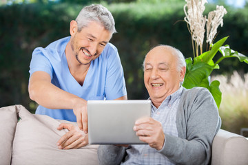 Male Nurse And Senior Man Laughing While Using Digital Tablet
