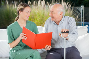 Smiling Female Nurse And Senior Man Looking At Each Other