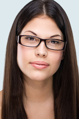 Brown hair, brown eyes, flawless face, bespectacled woman