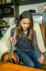 Young hipster girl with acoustic guitar at home