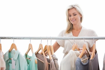 Pretty blonde looking through clothes rail