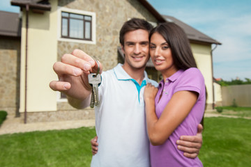 Couple in front of new home holding door keys.