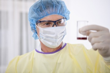 doctor in protective gear holding blood sample