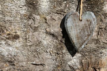 Grußkarte mit Herz aus Holz auf Steinhintergrund