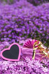 Postkarte aus Herz und Geschenk mit lila Blumen