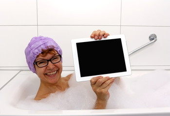 Enthusiastic mature woman in bathtub with tablet computers