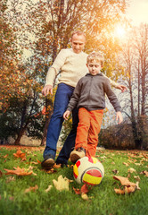 Father with son playing in football at the autumn park