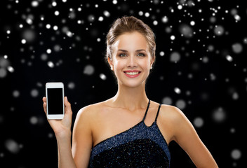 smiling woman in evening dress holding smartphone