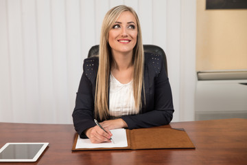 Portrait Of Attractive Businesswoman Reading Paper In Office
