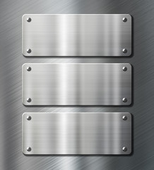 three stainless steel metal plates on brushed background