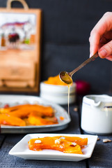 pour honey on a spoon baked pumpkin with walnuts