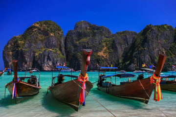 Long tail boat on white sand beach with crystal clear sea