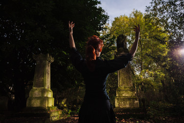 Redhead woman performing ritual at grave