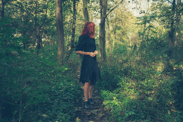 Young redhead woman in the woods