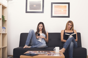 two women using mobile and reading a book on sofa in her home