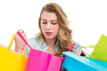 Blonde woman opening gift bag and looking on it