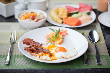 Hotel breakfast. Fried eggs with bacon and fruit
