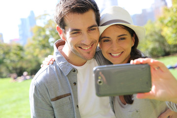 Cheerful couple taking picture of themselves in central park