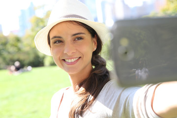 Beautiful woman with hat taking picture with smartphone