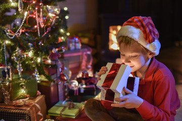 Lovely little boy with a santa claus hat opens a gift in front o