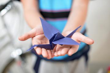 Origami crane in children's hands (soft focused)