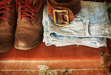 Pair of jeans, shoes, belt in a vintage suitcase