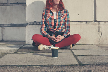 Woman sitting in street with paper cup