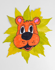 Autumn leaves with painted lion isolated on white