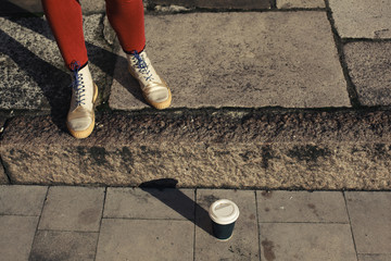 Feet and paper cup in street