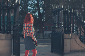 Young woman standing by gates