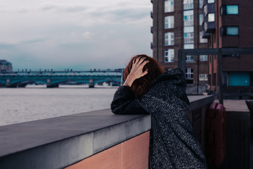 Sad woman by river in city