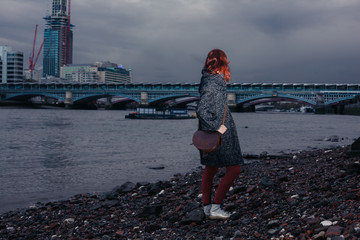 Young woman standing on river bank in city