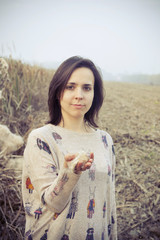 brunette girl in the countryside with dry field background