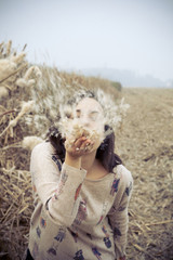brunette girl in the countryside blowing giant dandelion