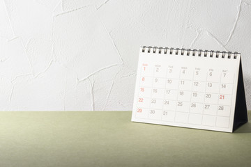 Desk.Calendar on Desk.Empty Wall of Stucco.