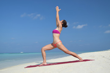 Asian chinese woman practising yoga by the sea