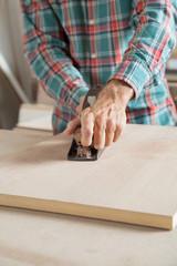 Male Carpenter Using Planer On Wooden Plank