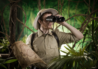 Explorer in the jungle with binoculars