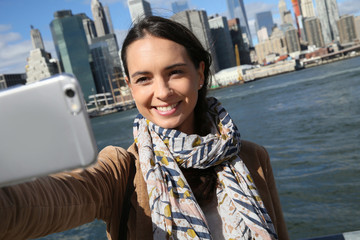 Brunette girl making selfy with Manhattan in background
