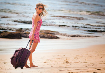 Woman carries your luggage at sandy beach