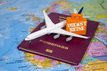 Reisepass mit Flugzeug und Koffer mit Dienstreise