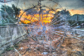 Broken glass by the street at sunset