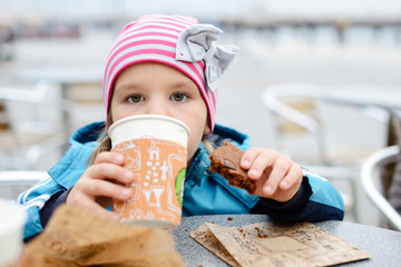 little girl drinking outdoors