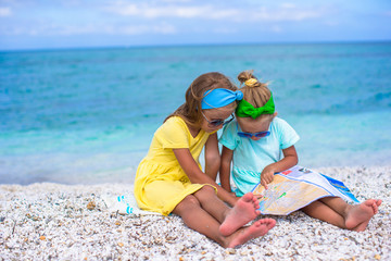 Little adorable girls with big map on tropical beach vacation
