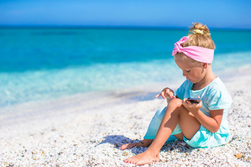 Little adorable girl playing in phone during beach vacation