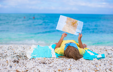 Adorable little girl with map find the way on tropical beach