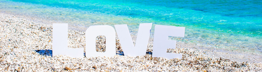 Word love on tropical beach background of turquoise sea and blue