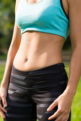 Fit woman showing her abdominal muscles