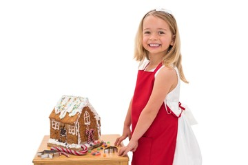 Festive little girl making gingerbread house